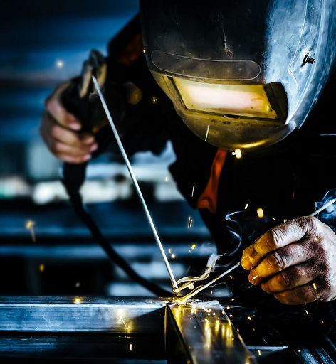 Professional mask protected welder man working on metal welding